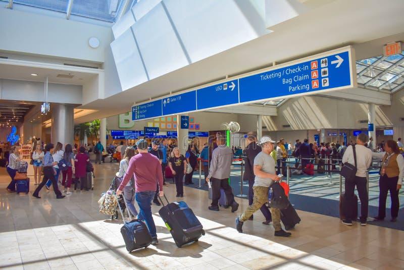 人们走到不同的终端和票顶视图的和报到蓝色标志在奥兰多国际机场4 免版税库存图片