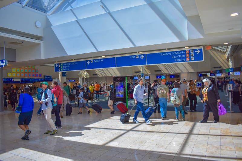 人们走到不同的终端和票顶视图的和报到蓝色标志在奥兰多国际机场1 免版税库存照片