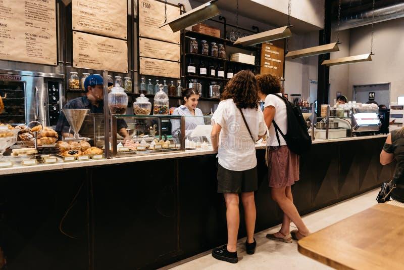 人们预定在减速火箭的被称呼的咖啡馆的柜台 免版税库存照片