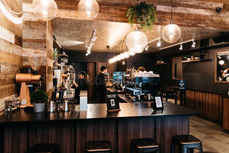 人们预定在减速火箭的被称呼的咖啡馆的柜台 库存照片
