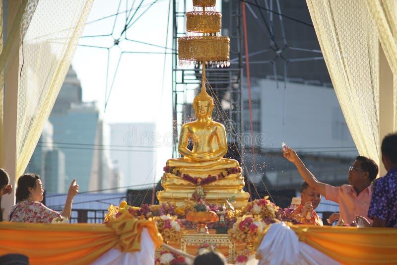 人们飞溅水和香水对菩萨雕象 免版税库存图片
