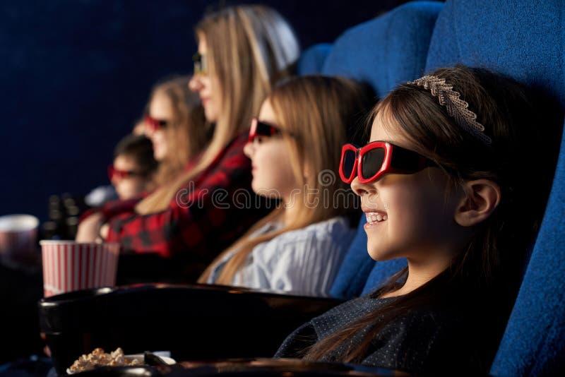 人们,孩子在3d玻璃的watchng电影在戏院 免版税库存照片