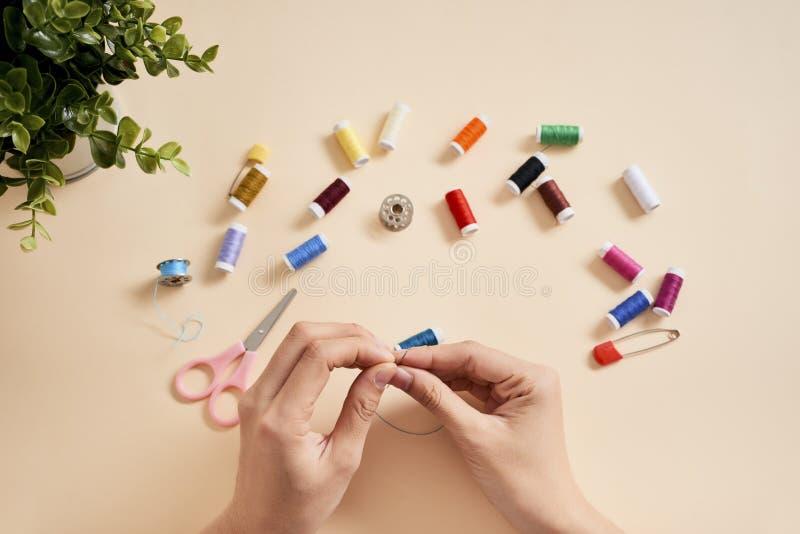 人们,针线,缝合和剪裁概念-有螺纹的裁缝妇女在针缝的织品 缝合与针的手 免版税库存图片