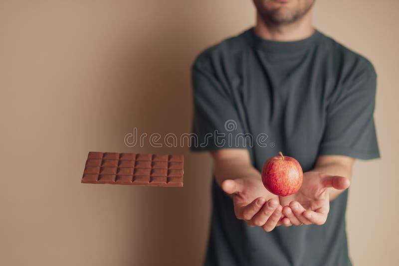 人位置在浮动苹果下递,当忽略巧克力块,时 库存照片