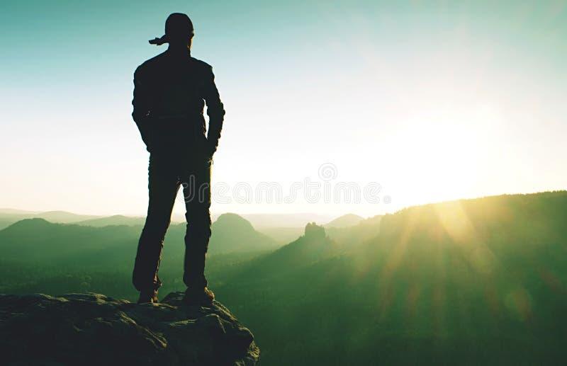 人体育jerzey享受山顶胜利 徒步旅行者观看太阳 免版税库存图片