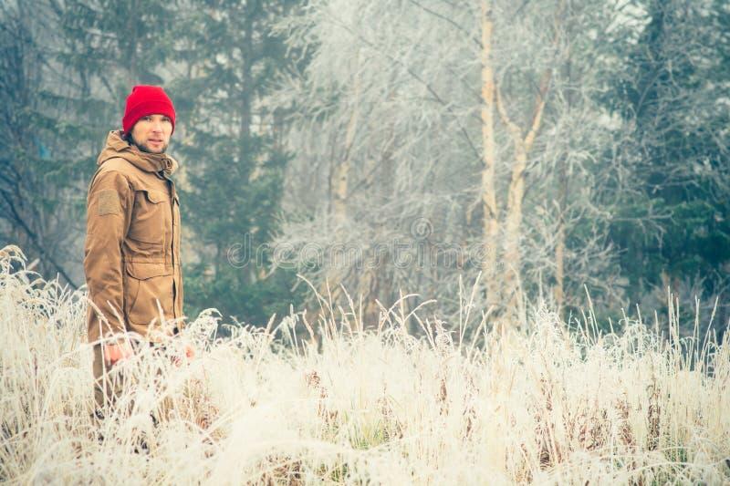 年轻人佩带的冬天帽子衣物室外与在背景旅行生活方式的有雾的森林自然 免版税库存照片