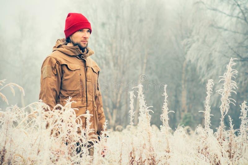 年轻人佩带的冬天帽子衣物室外与在背景旅行的有雾的森林自然 免版税库存照片