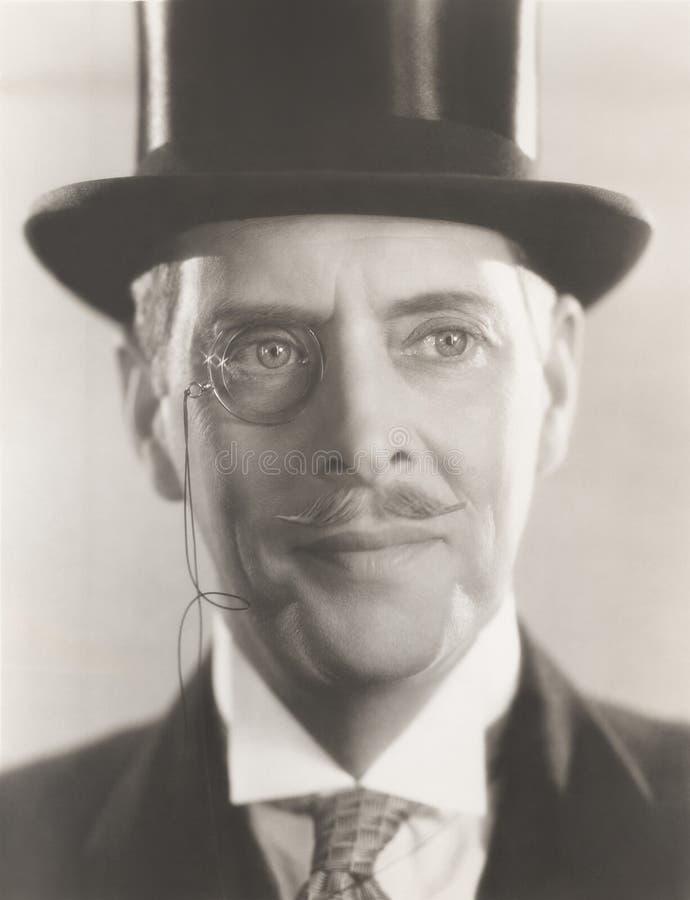 人佩带的单片眼镜和高顶丝质礼帽画象  免版税图库摄影