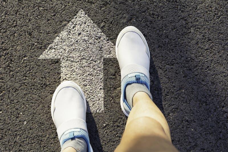 人佩带的白色鞋子顶视图选择方式的标记用白色箭头 选择正确的道路概念 免版税图库摄影