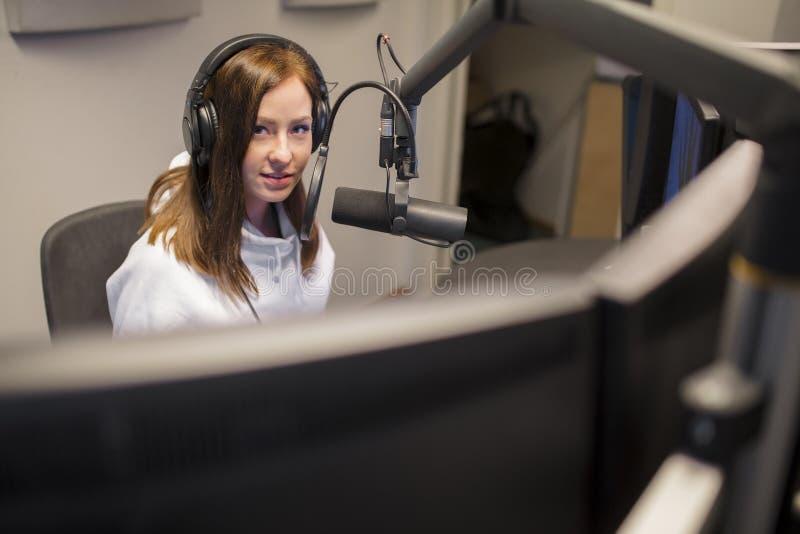 主人佩带的耳机,当使用话筒在无线电演播室时 免版税库存照片