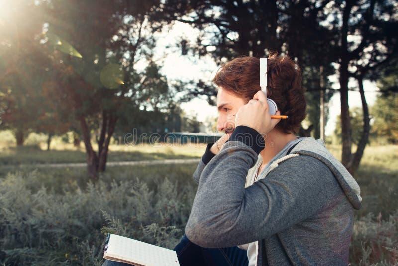 人佩带的耳机,放松在自然 库存照片