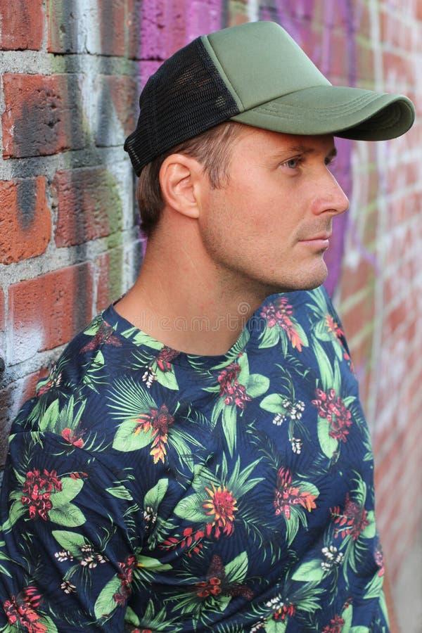 人佩带的衬衣外形有花卉样式和棒球帽的 免版税库存图片