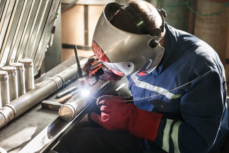人佩带的面具焊接特写镜头在车间 库存照片