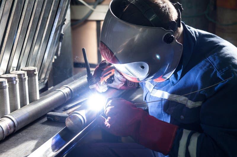 人佩带的面具焊接特写镜头在车间 库存图片