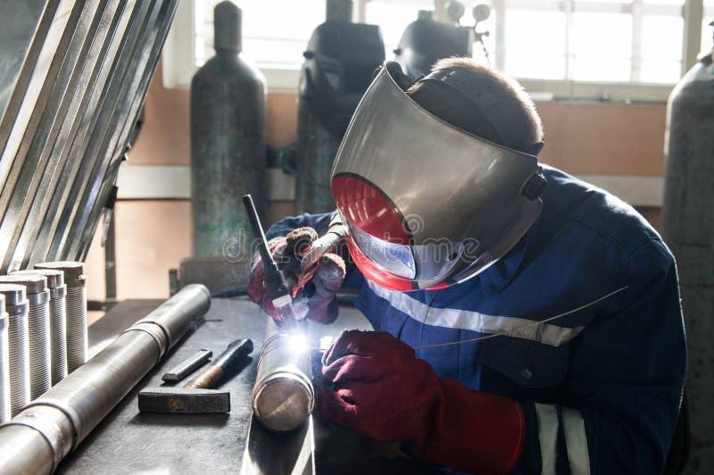 人佩带的面具焊接特写镜头在车间 免版税库存图片