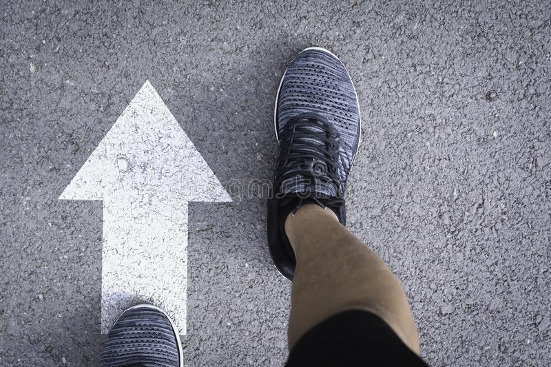 人佩带的鞋子顶视图选择方式的标记用白色箭头 选择正确的道路概念 库存图片