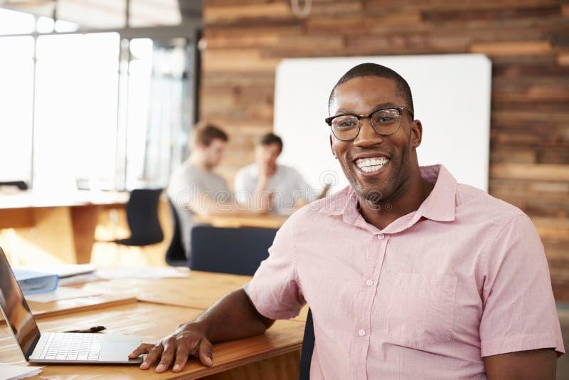 年轻黑人佩带的玻璃在看对照相机的办公室 库存图片