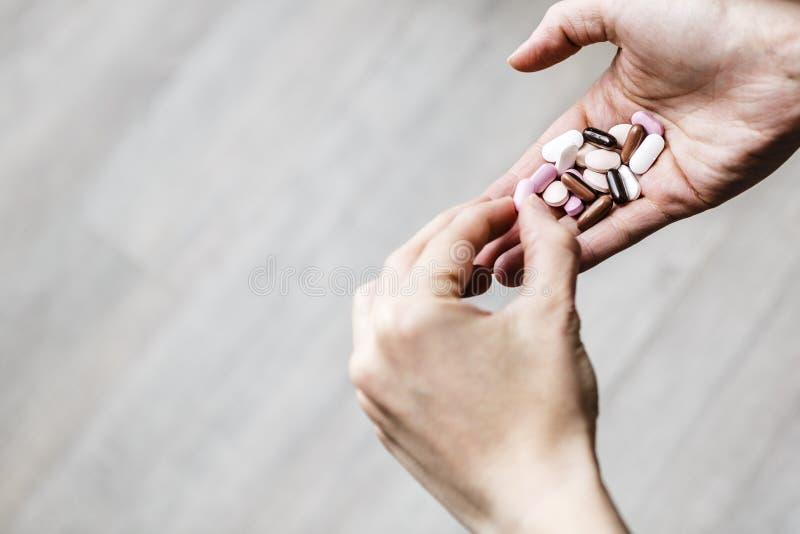 年轻人使上瘾的妇女决定吃的药物哪个药片  库存图片