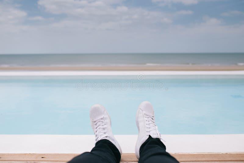 人使变冷的放置在水池旁边和看看海和海滩 免版税库存图片
