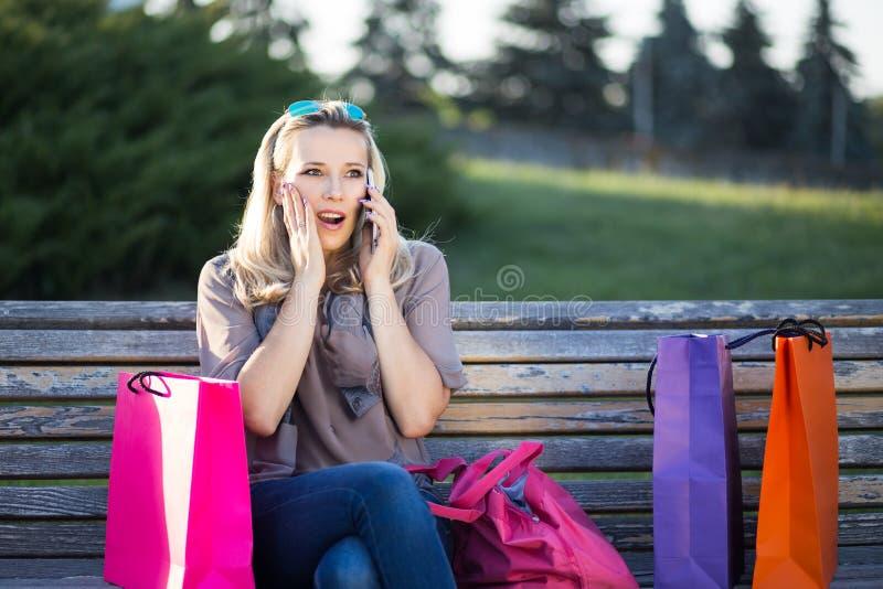 年轻人使妇女惊奇坐长凳在购物以后 免版税库存照片