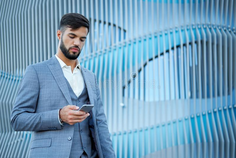 人使用一个智能手机 使用手机的商人都市专业商人 愉快的专业佩带的衣服夹克 免版税库存图片