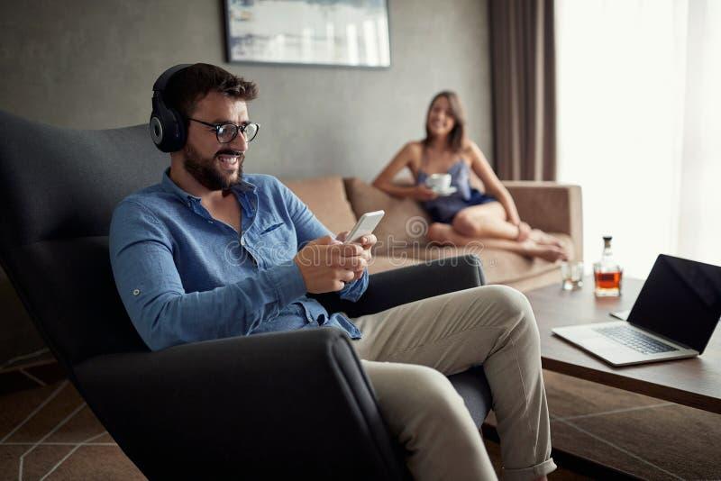 人使用一个电话听到音乐和在家放松 库存图片