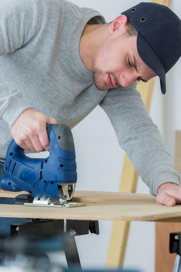 人使用带锯的切口woodplank 免版税库存图片