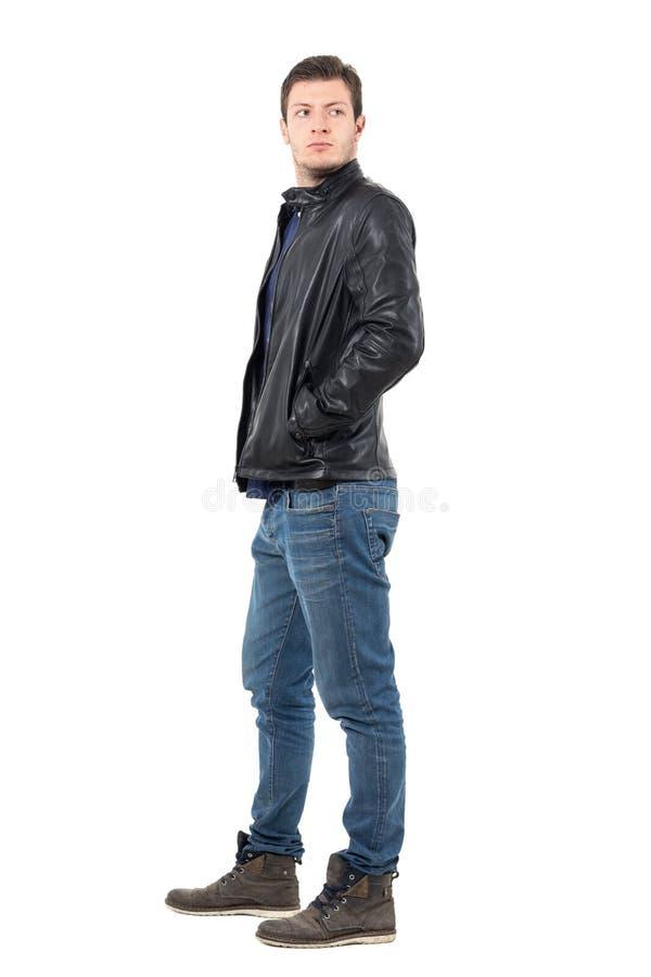 年轻人侧视图回顾在肩膀的皮夹克和牛仔裤的 免版税库存照片