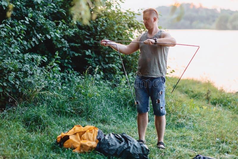 人修建帐篷本质上在日落的在钓鱼期间的湖附近 免版税图库摄影