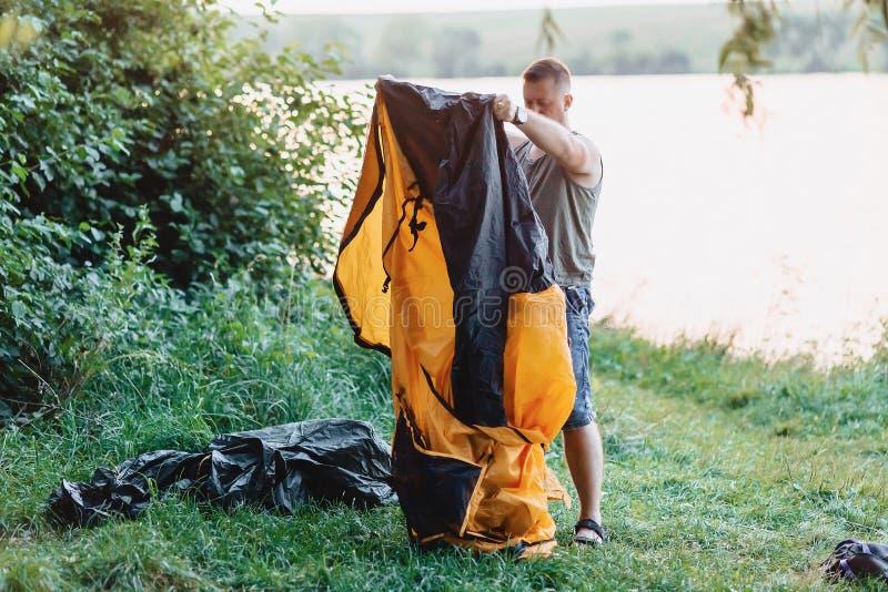 人修建帐篷本质上在日落的在钓鱼期间的湖附近 图库摄影