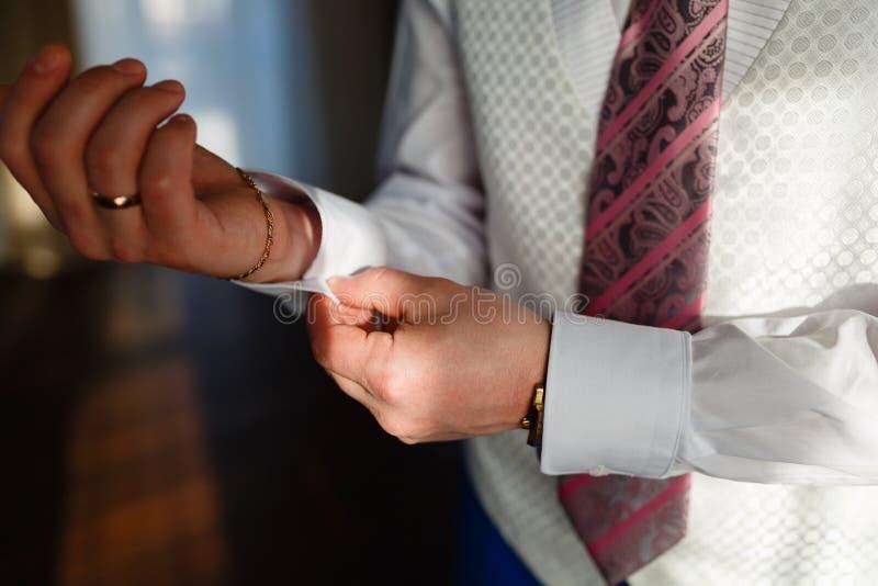 人修理在白色衬衣和时髦的背心和蓝色裤子的袖口有昂贵的金子辅助部件、手表、圆环和rin的 免版税图库摄影