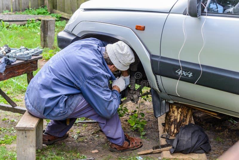 人修理在领域的汽车 免版税库存照片