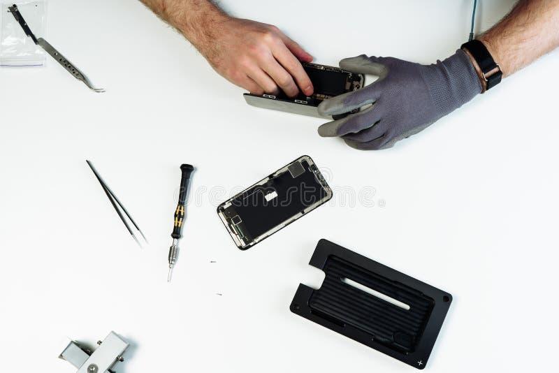 人修理被拆卸的残破的智能手机平的位置 免版税图库摄影