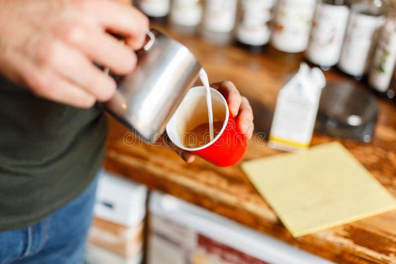 人倾吐从金属杯子的奶油入在一个红色杯子的一热的可口拿铁 专业barista做在葡萄酒咖啡的咖啡 库存照片