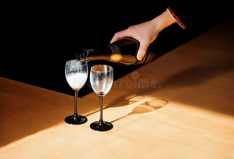 人倾吐的香槟到在某些欢乐的事件或结婚宴会的一块玻璃里 库存图片