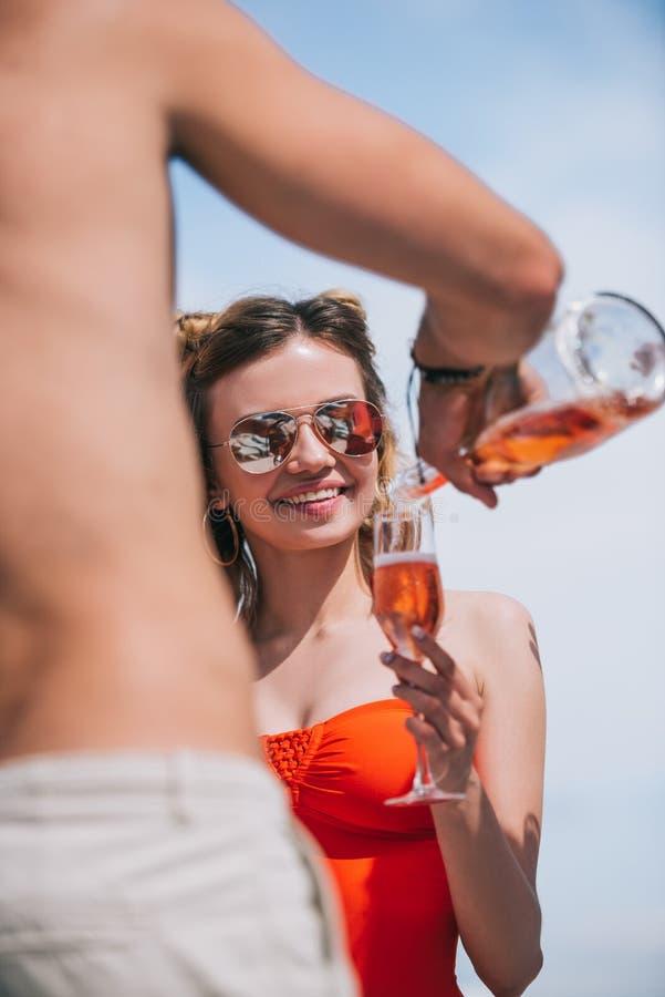 人倾吐的香槟播种的射击对微笑的年轻女人的 库存图片
