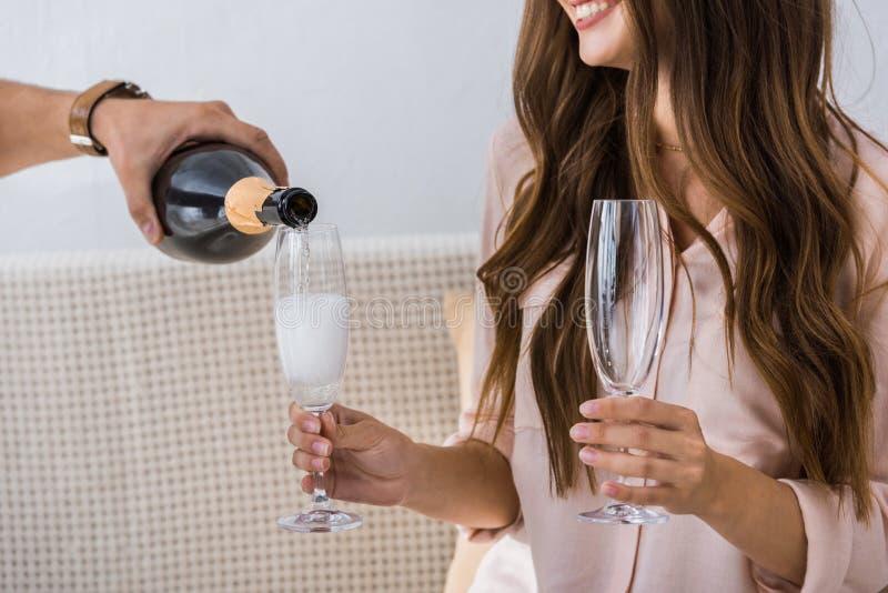 人倾吐的香槟的播种的图象到玻璃里,当他的女朋友时 免版税库存图片