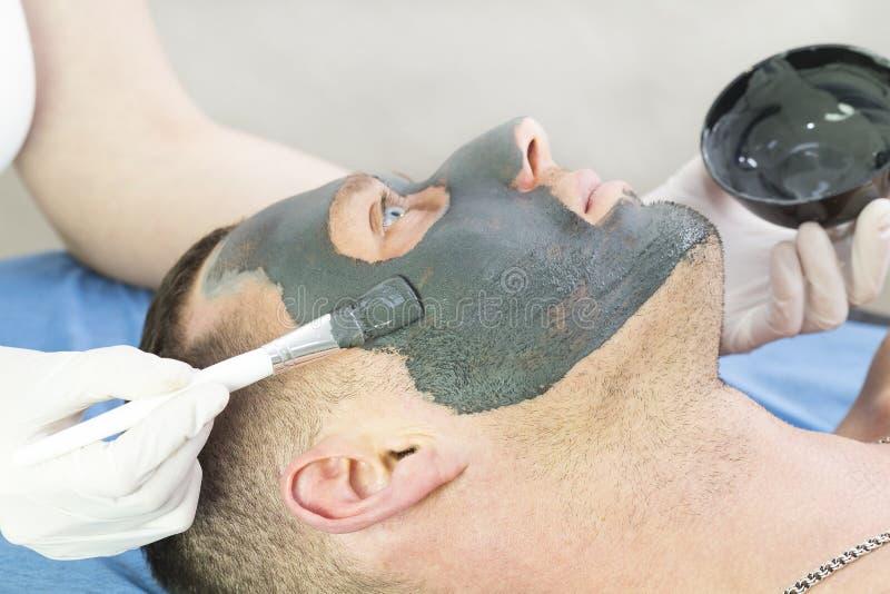 人做清洗他的面孔的做法与在美容院的黏土面具 免版税图库摄影