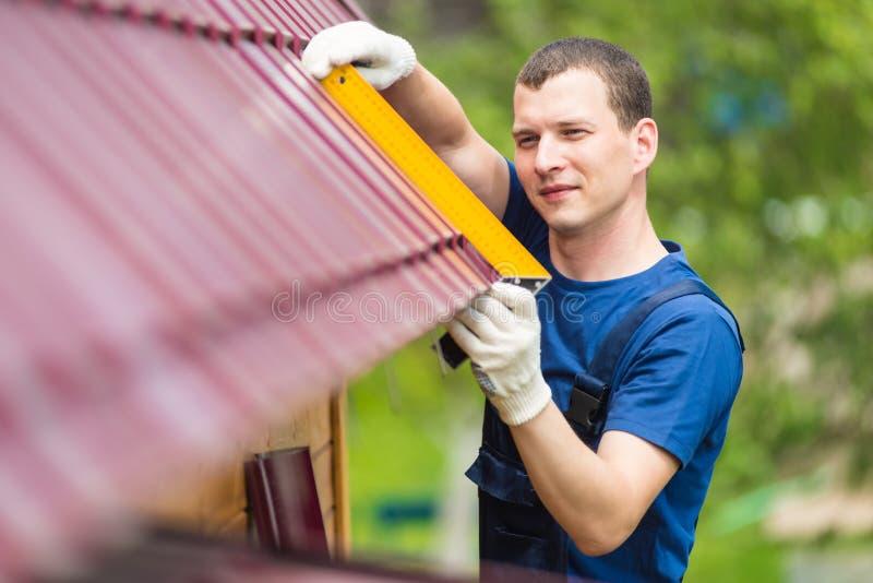 人做着在新的红色屋顶的一检查 免版税库存照片