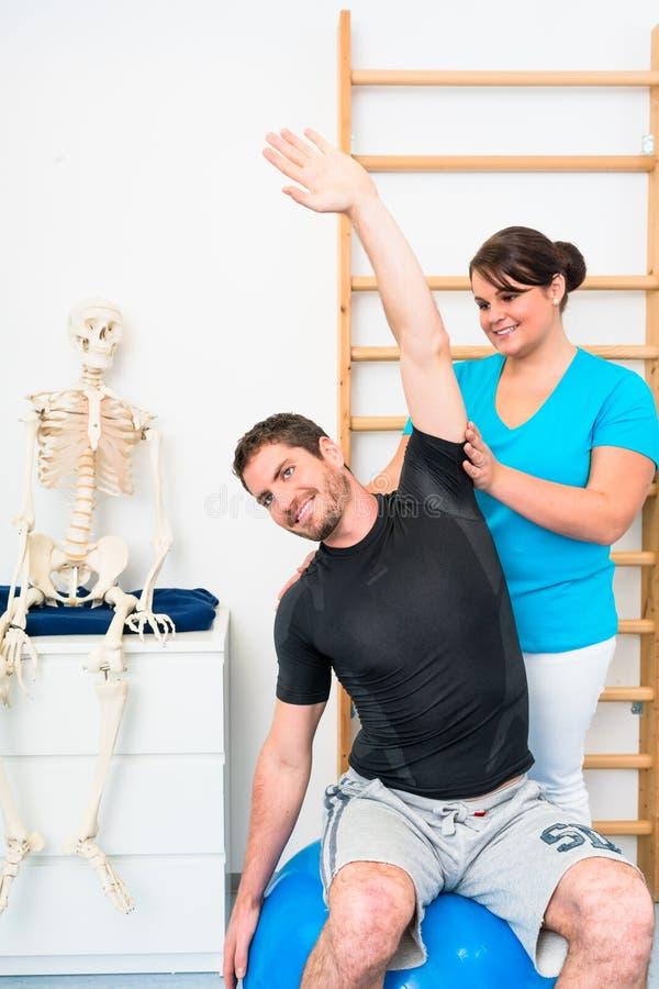 年轻人做舒展与生理治疗师的锻炼 库存照片