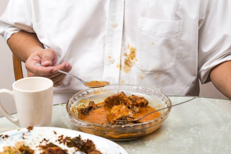 人偶然地溢出了在白色衬衣上的咖喱污点 库存图片