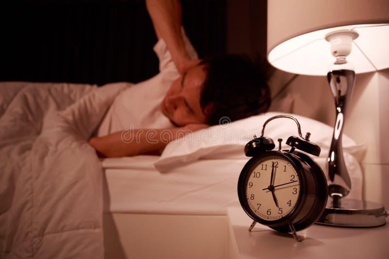 人关闭用手他的耳朵从闹钟噪声在床上的 免版税库存图片