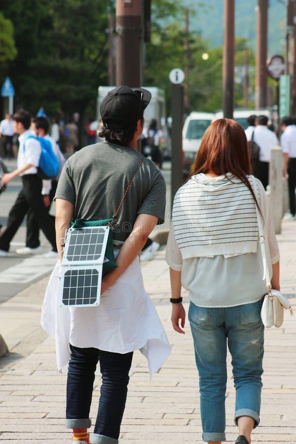 年轻人再充电智能手机,当走在街道上时 免版税库存图片