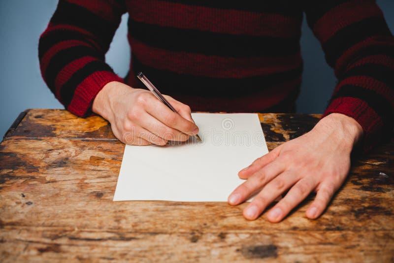 年轻人写着一封信 免版税图库摄影