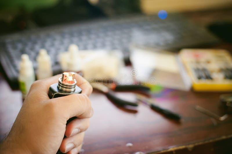 人准备卷电子吸烟鲜美vape汁液 免版税库存照片