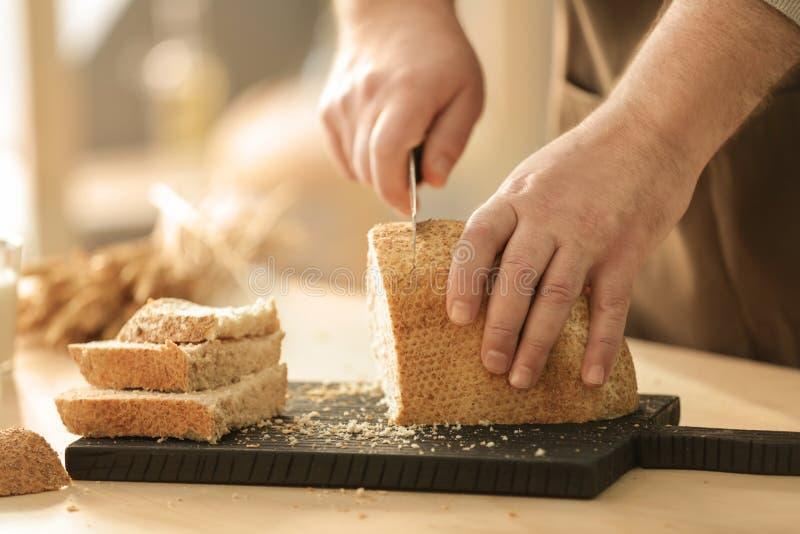 人切口面包的手 库存图片
