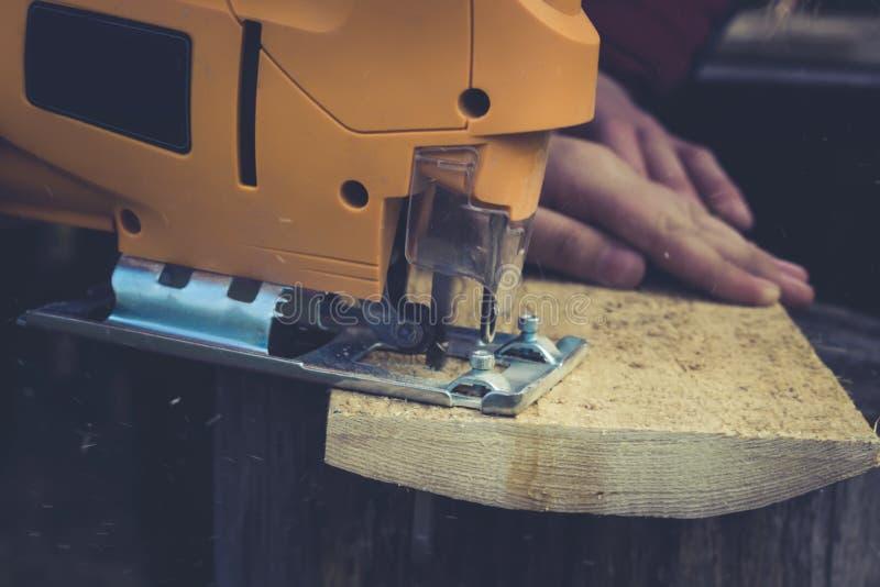 人切开木制品,使用电竖锯户外 特写镜头 免版税库存照片