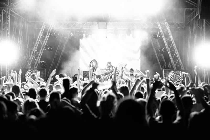 人剪影一个音乐会的在明亮的光的场面前面 黑色白色 图库摄影