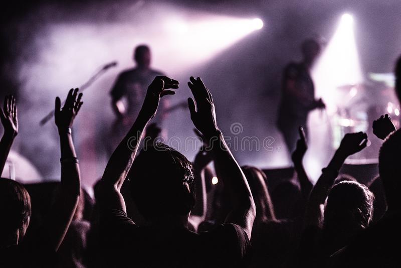 人剪影一明亮的在阶段前面的流行音乐摇滚乐音乐会 有姿态垫铁的手 那晃动 在a的党 图库摄影