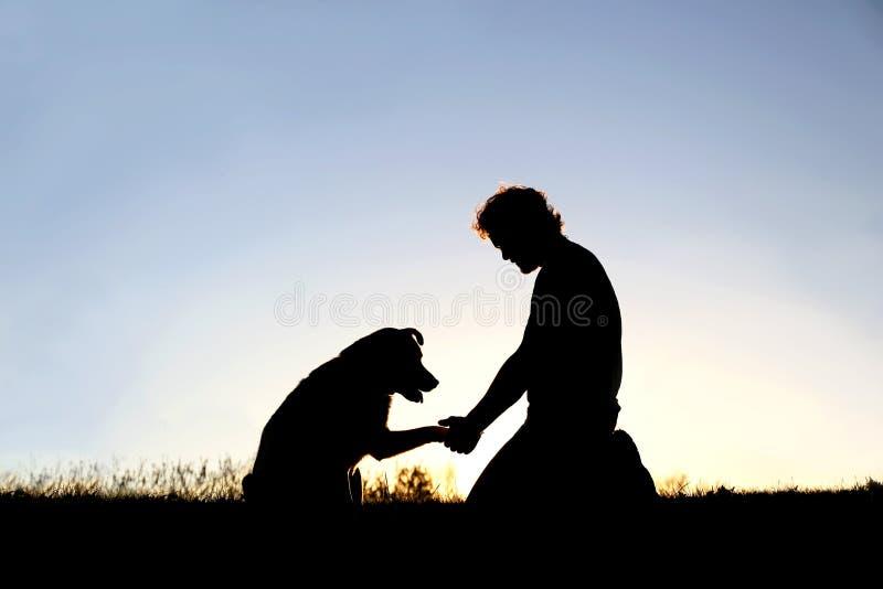 人剪影与他忠诚的爱犬握手 库存图片